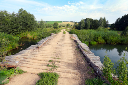 summer landscape old wooden bridge over a small river on a cloudy day photo