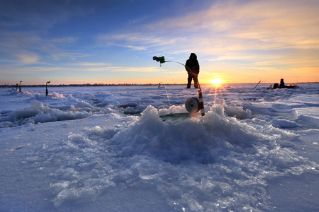winter landscape fishermen on the ice of the river at sunset photo