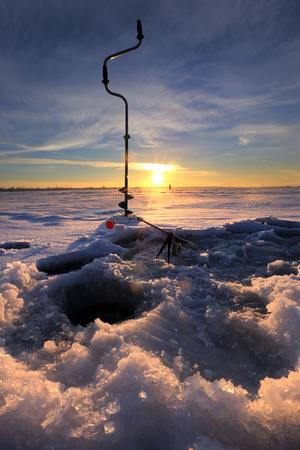close-up drill, fishing rod near the hole on the ice in winter river at sunset photo