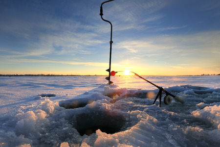 close-up drill, fishing rod near the hole on the ice in winter river at sunset Stockfoto