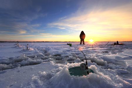 winter landscape fishermen on the ice of the river at sunset Standard-Bild