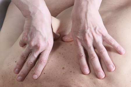 masseur: Isolated close-up of the hands of the masseur - female on mans back during a session, studio