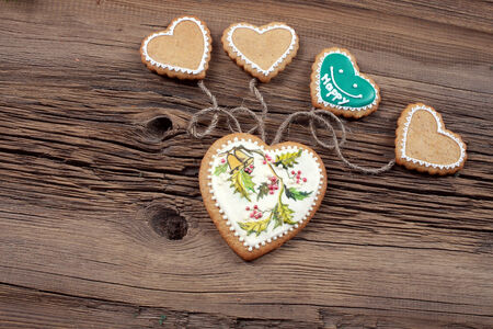 coupled: close-up of cookies in the shape of heart coupled with string on the background old boards studio