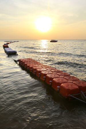 floaters: close-up floating barriers on the sea at sunset