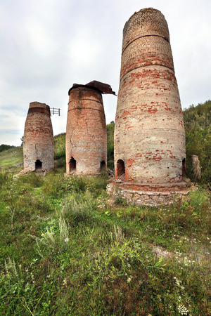 crumbling: abandoned crumbling furnaces of red brick in the Urals in the summer