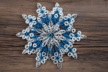 close-up of a snowflake out of paper quilling technique against the background of the old cracked board photo