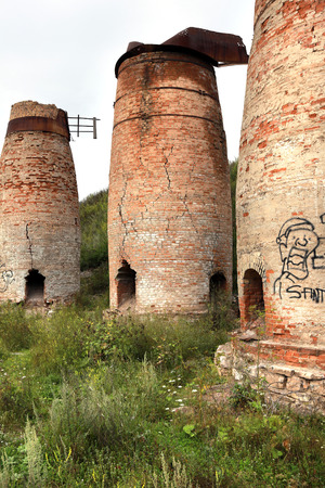 scrub grass: abandoned crumbling furnaces of red brick in the Urals in the summer