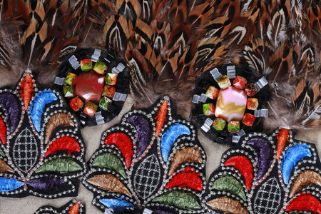 bead embroidery: macro texture fragment costume decorated with feathers, embroidery, beads in studio Stock Photo