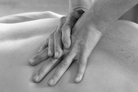 alternative therapies: Isolated close-up of the hands of the masseur - female on mans back during a session, studio
