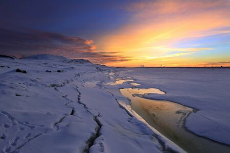 kama: winter landscape sunset on the ice of the river and the city on the horizon