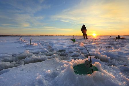 winter landscape fishermen catch fish on a frozen river at sunset photo