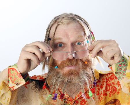 close-up portrait of an adult male with long beard, mustache and hair braided in pigtails gesturing studio on light background Stock Photo