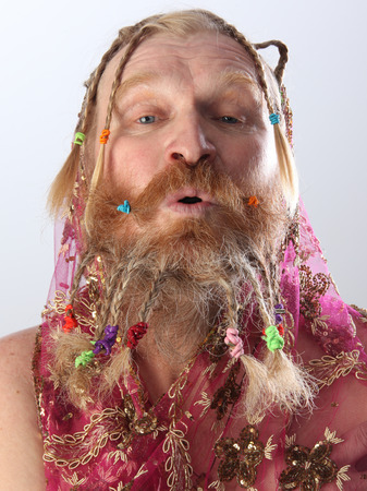 portrait of a man with a long beard, mustache and hair braided in pigtails playing with pink translucent scarf studio on light background Imagens