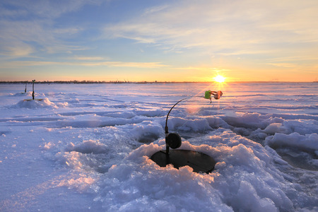 kama: winter landscape the rod on the river near  hole at sunset