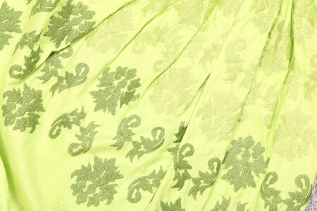 crease: close-up fragment green skirt in the crease with floral ornaments Stock Photo