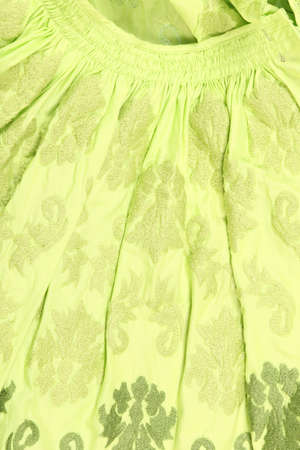 synthetic fiber: close-up fragment green skirt in the crease with floral ornaments Stock Photo