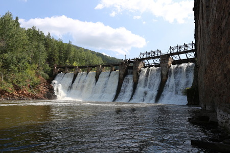 powerplant: summer landscape of the old dam on the river on a background of mountains and woods on a sunny day Stock Photo