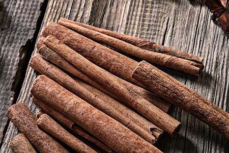 cannelle: close-up isolated cinnamon sticks on a background of the old board studio