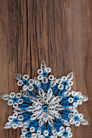 close-up of a snowflake out of paper quilling technique against the background of the old cracked board studio photo