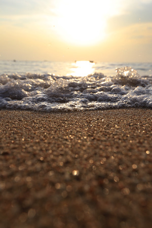 close-up texture of sea sand and surf line at sunset, low angle view