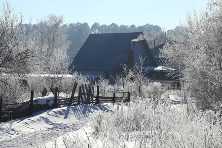 winter landscape frosty morning in the village, the frost on trees, fences and snow-covered road on a sunny day photo