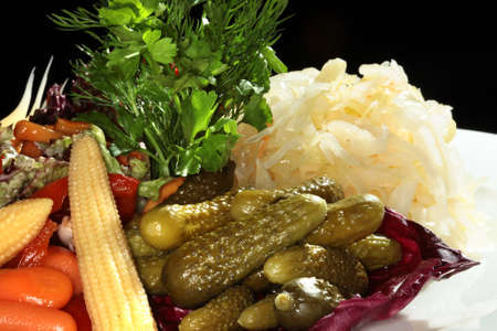 verdure: close-up of assorted pickles on a white plate decorated with verdure