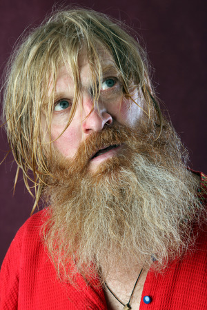 dramatic characters: close-up portrait of the blessed with a long beard and a mustache and wet blond hair in a red shirt studio Stock Photo
