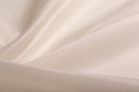 satin background: macro texture of satin fabric champagne-colored studio