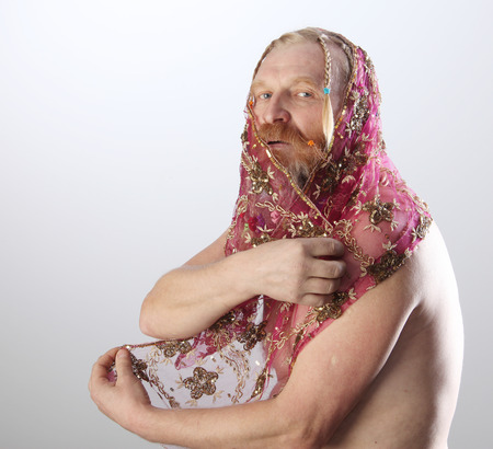portrait of a man with a long beard, mustache and hair braided in pigtails playing with pink translucent scarf studio on light background Stock Photo