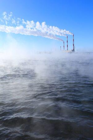 winter landscape smoke from the chimneys Zainsk TPP against the blue sky frosty misty morning photo