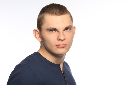 imperturbable: close-up portrait of a young man in a blue shirt on a white background studio Stock Photo