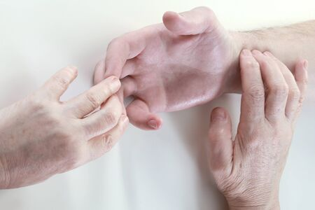 acupressure hands: close-up masseurs hands during operation on a white background studio