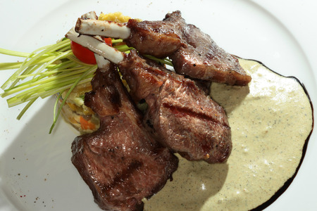 second meal: macro meat on the bone grilled with vegetables and cream sauce on a white plate Stock Photo