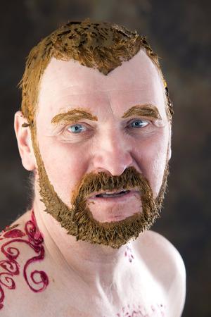 calavera caricatura: Close-up retrato de un macho adulto con un torso y el cuerpo de pintura con henna y cabello de color y estudio barba