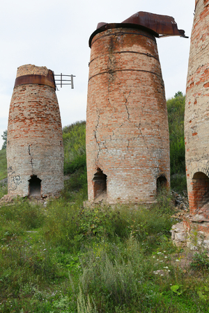 broken hill: abandoned crumbling furnaces of red brick in the Urals in the summer