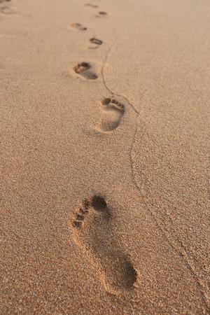 close-up van menselijke voetafdrukken in het natte zand op het strand