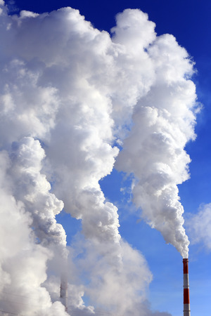 thermal pollution: isolated close-up of white smoke from the chimney of the plant against the blue sky