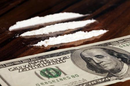 drogadiccion: primer plano de billetes y polvo blanco en una mesa de madera, estudio