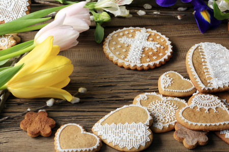 macro gingerbread heart-shaped with a yellow ribbon, flowers on wood background studio photo