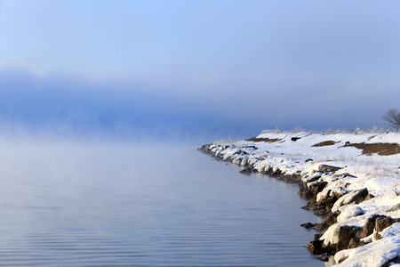 winter landscape dense fog over the river early in the morning at sunrise photo