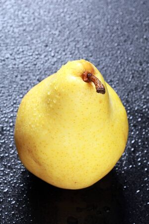 macro one yellow pear with drops of dew on a black background studio photo