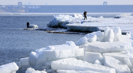 ice dam: landscape Fishermen catch fish on the ice of a large reservoir in the early spring ice drift Stock Photo