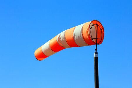 windsock: close-up of orange windsock on blue sky background