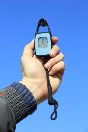 anemometer: close-up anemometer in hand on blue sky background
