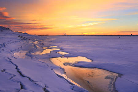 winter landscape sunset on the ice of the river and the city on the horizon