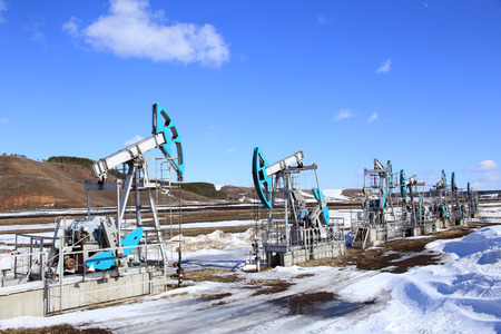 industrial landscape Oil pumps in the field on a background of blue sky and white clouds on a sunny day in early spring photo