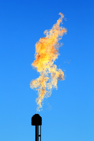 close-up oil burning torch against the blue sky photo