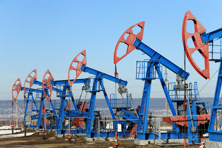 industrial landscape oil pumps in the early spring on a blue sky background photo