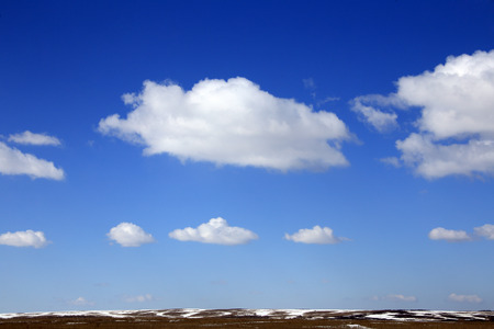 marvelous: landscape marvelous white clouds in the blue sky above snow-covered field in early spring