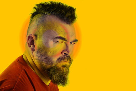close-up portrait profile of a angry white man with mohawk and beard Stock Photo